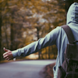 white person wearing hoodie and backpack while hitchhiking on a road going through a forest