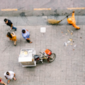 overhead shot of city street, people walking around a food cart while a man sweeps trash
