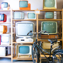 store shelves filled with CRT TVs of various sizes; a bicycle sitting in the middle of the store