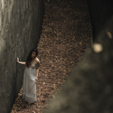 woman in white dress standing on brick path beside rock wall