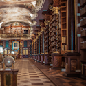 oppulent library in Prague, grand gallery with a mural on the ceiling, bookshelves lining the walls, and displays along the gallery showing globes and scientific instruments