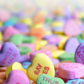 close up picture of candy hearts with messages of love written on them