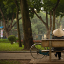 a person wearing a rattan hat sitting on a bench with a bicycle next to them in Vietnam