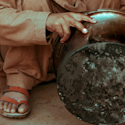 a boy in Pakistan crouching next to a pot and other cookware