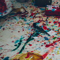 blue, red, yellow, and green paint splattered over a white drop cloth and paint bottles