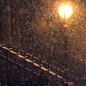 a person with a hood up walking on a street illuminated by streelights at night with falling snow