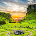 a green valley with concentric circles of grass and dirt centered on a pile of rocks like an altar at sunrise