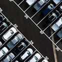 an aerial shot of a parking lot of black, white, and gray cars with one red car