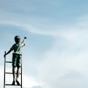 boy standing on a ladder reaching for the clouds