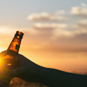 two people clinking brown bottles in front of a sunset