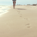 woman walking on a beach leaving distinctive footprints in the sand