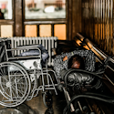 gray wheelchair beside person sleeping on bench